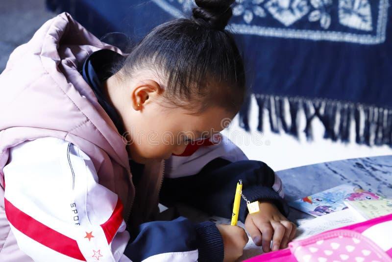 Une petite fille faisant des leçons d'école dans le village de Zhoucheng, Dali, Yunnan, Chine photographie stock libre de droits