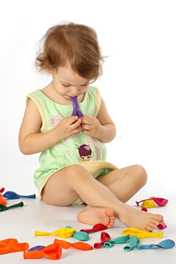 Une petite fille gonfle des ballons. photo libre de droits