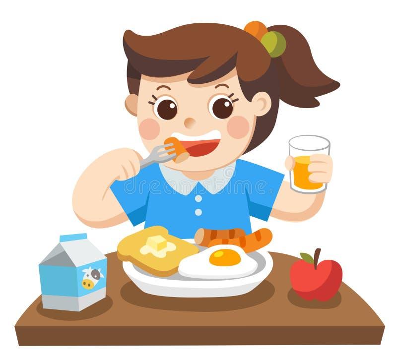 Une petite fille heureuse de manger le petit déjeuner pendant le matin photos libres de droits