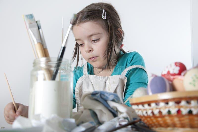 Une petite fille heureuse peignant des oeufs de pâques images libres de droits