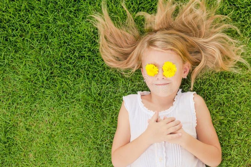 Une petite fille heureuse se trouvant sur l'herbe image stock