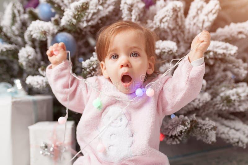 Une petite fille joue avec une guirlande avec un arbre de nouvelle année Danger Enfant désobéissant Bon esprit de nouvelle année photographie stock libre de droits