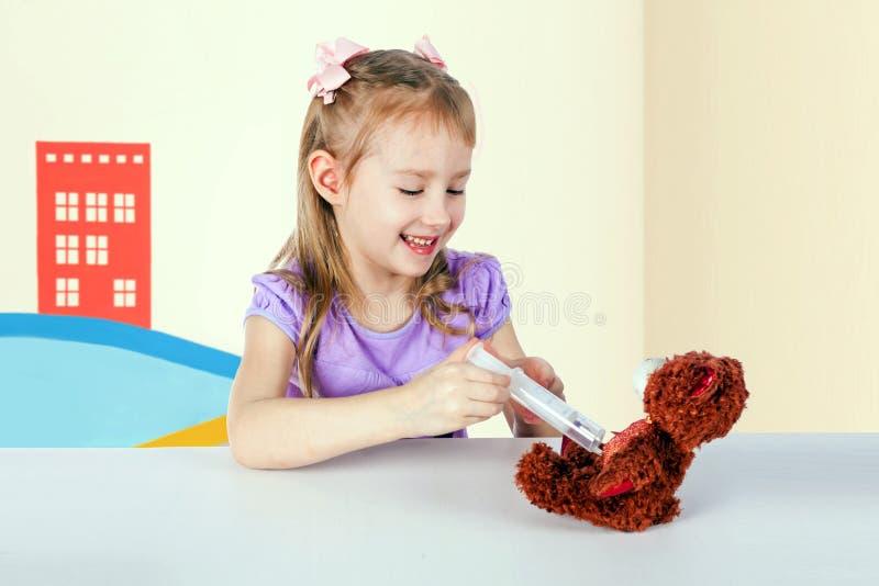 Une petite fille joue le docteur - elle injecte un ours de jouet photos stock
