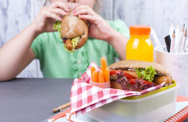Une petite fille mange son déjeuner à l'école Écolière de déjeuner Grillez et et jus et salade frais pour un dîner sain libre image stock