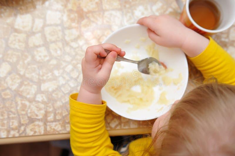Une petite fille mange son dîner à la table photo stock