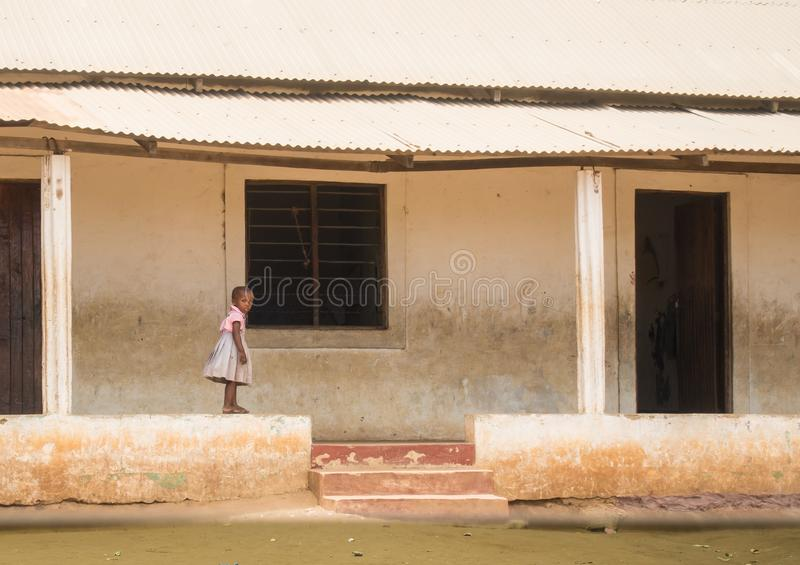 Une petite fille marche sur le mur de l'école au Kenya images libres de droits