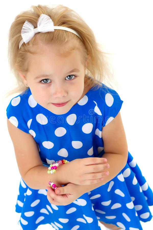 Une petite fille met un bracelet sur son bras photos libres de droits