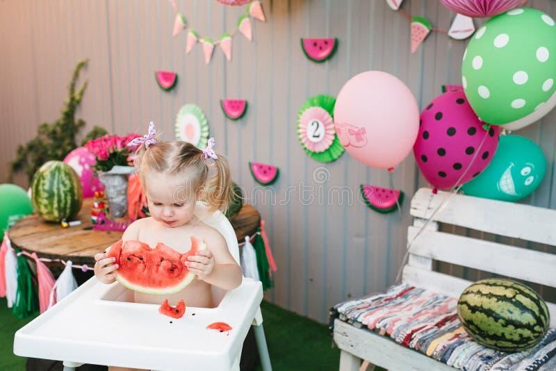 Une petite fille mignonne une blonde de bébé mange une pastèque juteuse dans l'arrière-cour célébrant un anniversaire photographie stock libre de droits