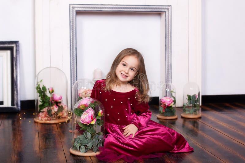 Une petite fille mignonne dans une robe s'assied sur le plancher avec une rose dans un flacon Regarder l'appareil-photo Enfance P image stock