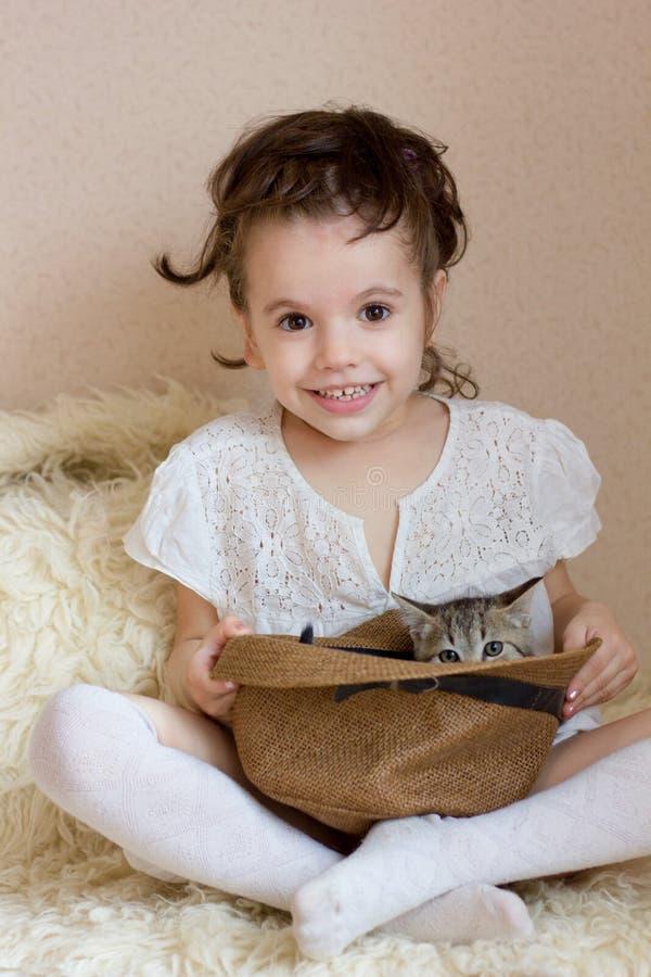 Une petite fille mignonne joue avec un chaton dans un chapeau photo stock