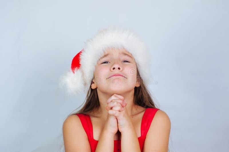 une petite fille mignonne se tient dans un chapeau de Noël pour demander un cadeau images stock