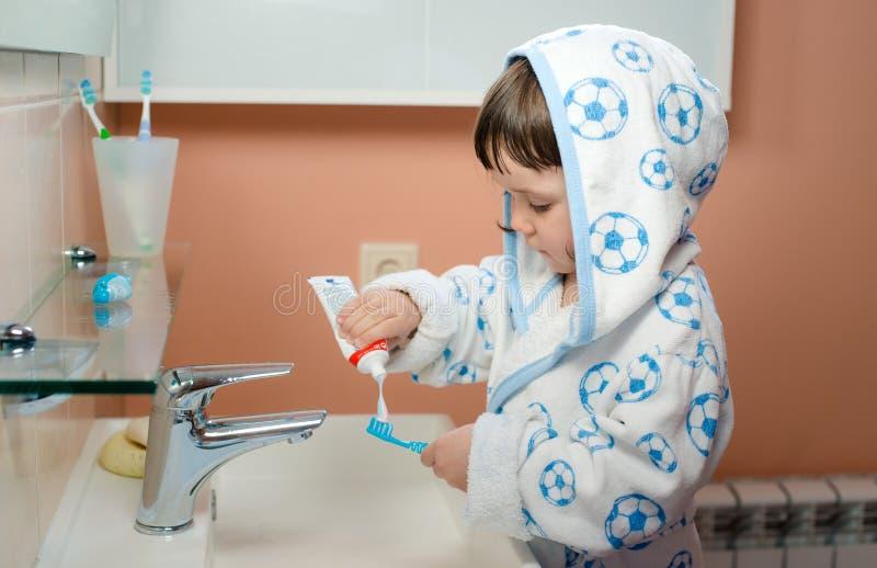 Une petite fille ou un enfant brosse des dents dans la salle de bains Hygiène de la cavité buccale photos libres de droits