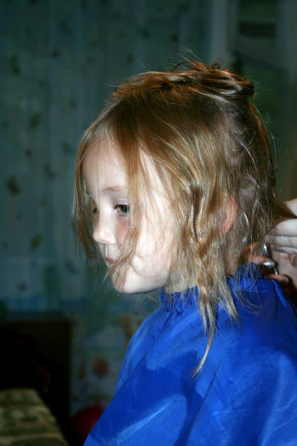 Une petite fille pendant le processus de coupe de cheveux photos stock