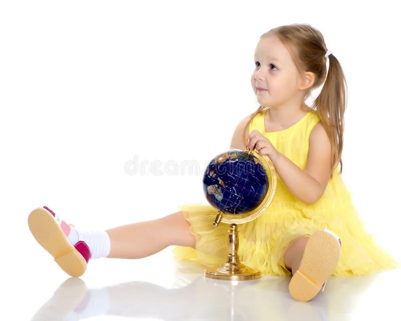 Une petite fille regarde le globe photographie stock libre de droits