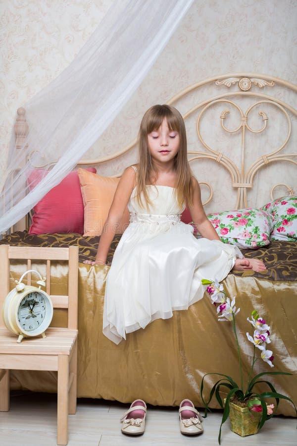 Une petite fille s'asseyant avec des yeux s'est fermée sur le lit photographie stock libre de droits