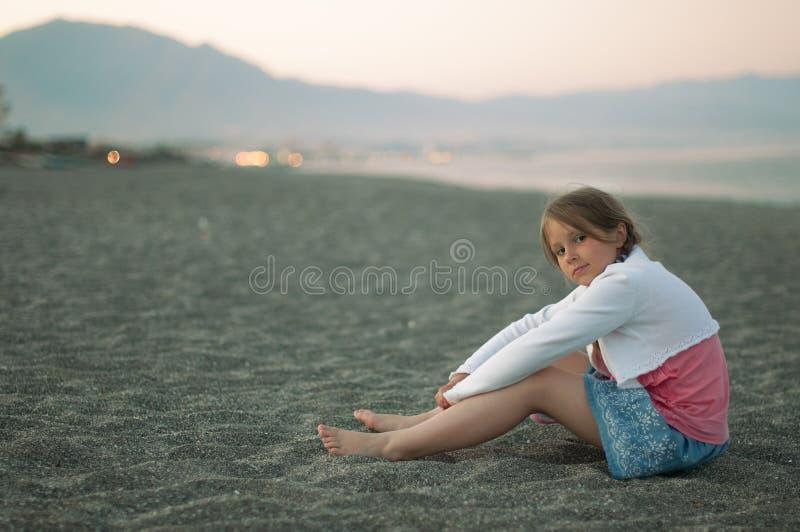 Une petite fille s'asseyant sur un Pebble Beach dans le temps de soirée image stock