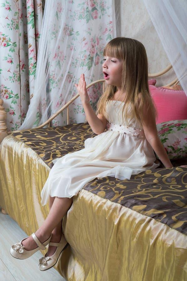 Une petite fille s'assied sur un grand lit images stock