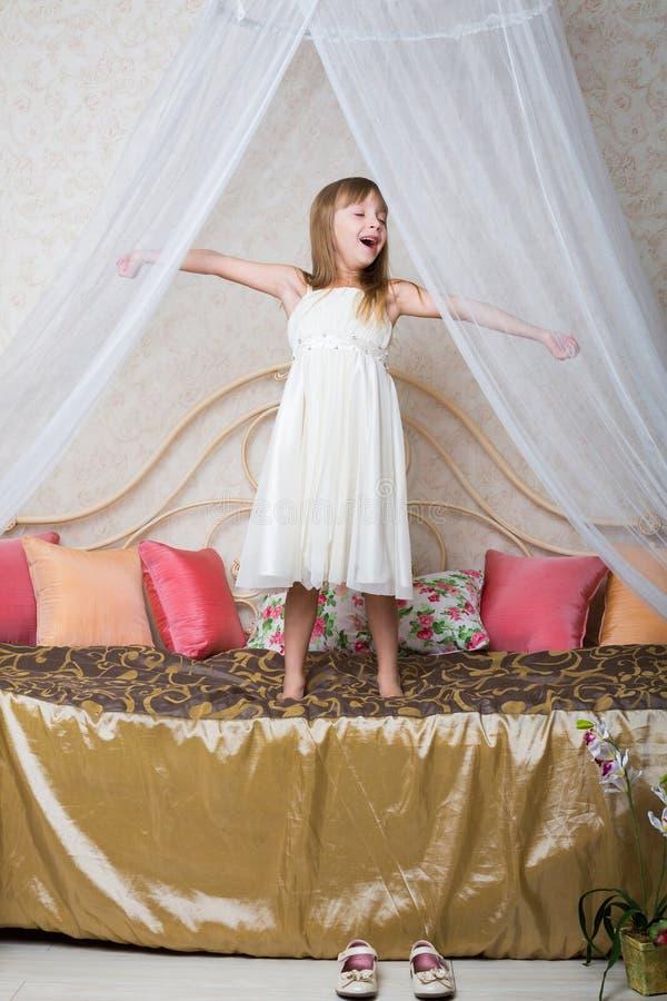 Une petite fille se tenant sur le grand lit images libres de droits