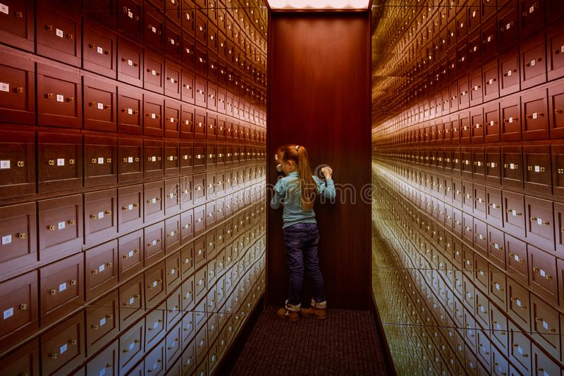 Une petite fille se tient dans la chambre des illusions La salle s?re est une salle multicolore des illusions Une salle des illus image libre de droits