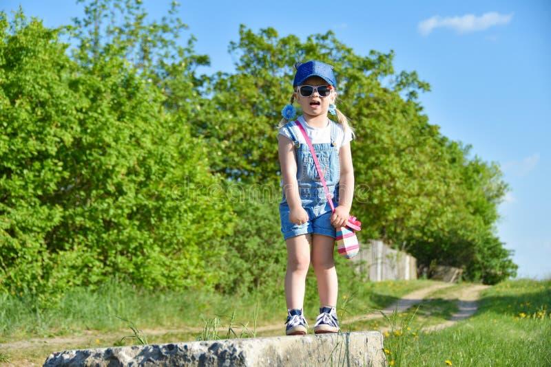 Une petite fille se tient sur un vieux bloc de béton, pleurer, effrayé des tailles, crainte images libres de droits