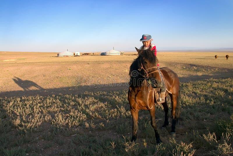 Une petite fille sur un cheval en steppe mongole image libre de droits