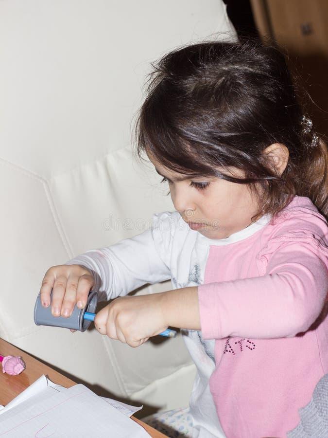 Une petite fille tient un crayon et un taille-crayons portrait en gros plan d'une fille de trois ans photos libres de droits