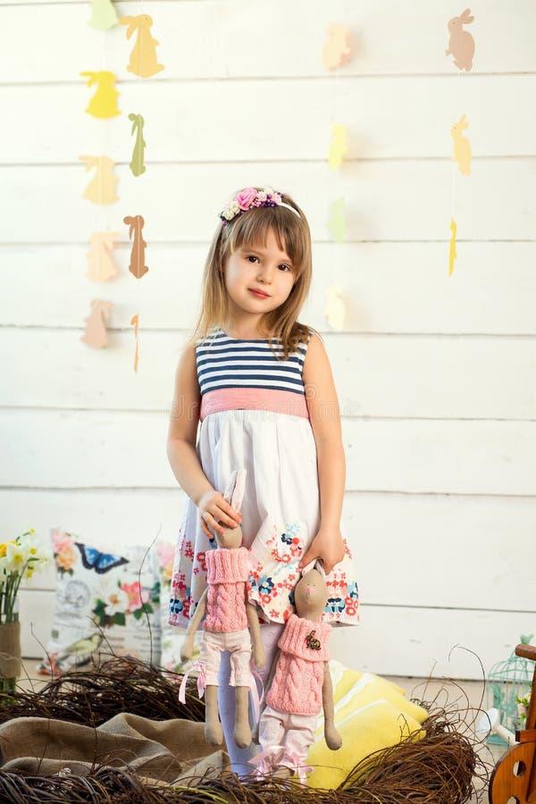Une petite fille triste dans une robe avec des fleurs sur sa tête se tient dans un nid et tient les lapins mignons de jouet par l images stock