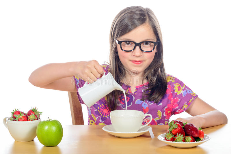 Une petite fille verse le lait dans une tasse photo libre de droits