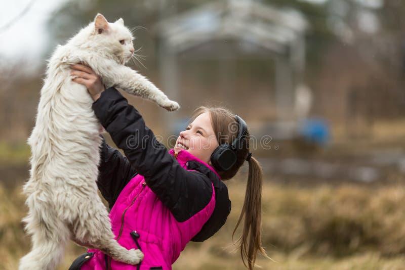 Une petite fille vilaine dans des écouteurs jouant avec le chat nature images libres de droits