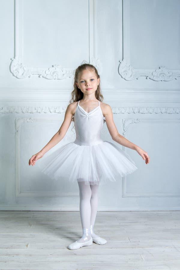 Une petite jeune ballerine adorable dans une humeur espiègle dans l'inter photographie stock