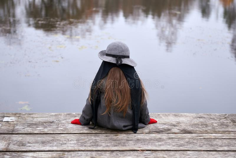 Une petite jolie fille s'asseyant sur un pont image stock