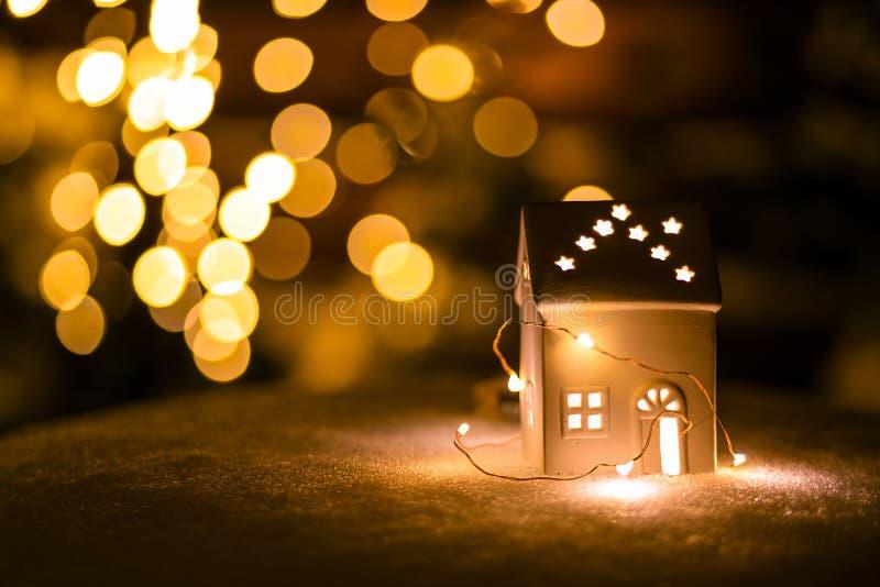 Une petite maison avec des étoiles sur la neige pendant la nuit avec le fond de boche photos libres de droits