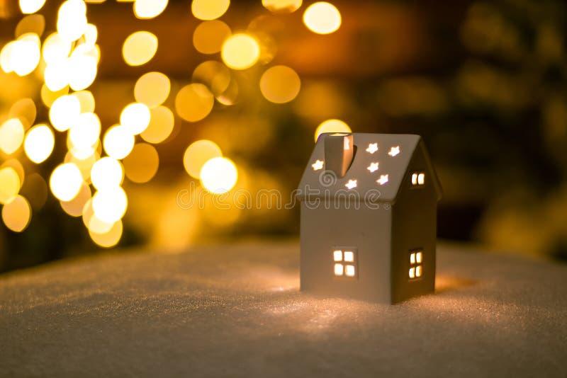 Une petite maison avec des étoiles sur la neige pendant la nuit avec le fond de boche photo stock