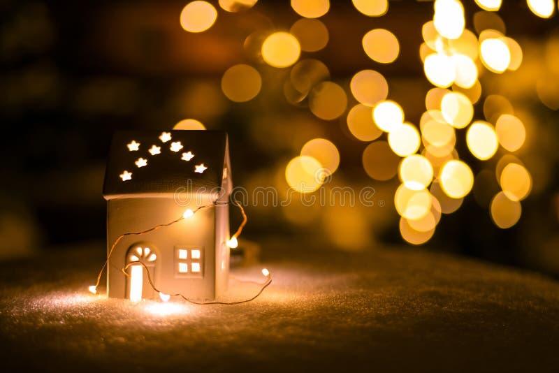 Une petite maison avec des étoiles sur la neige pendant la nuit avec le fond de boche images stock