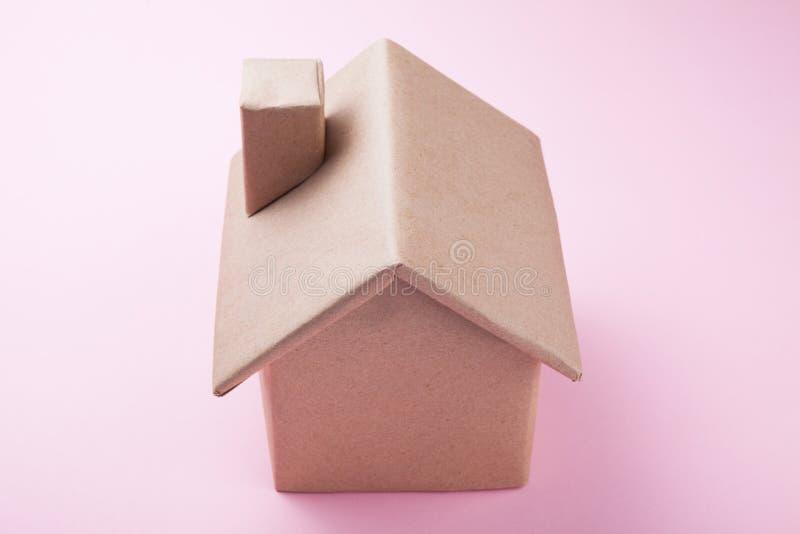 Une petite maison de papier sur une belle surface rose photo stock