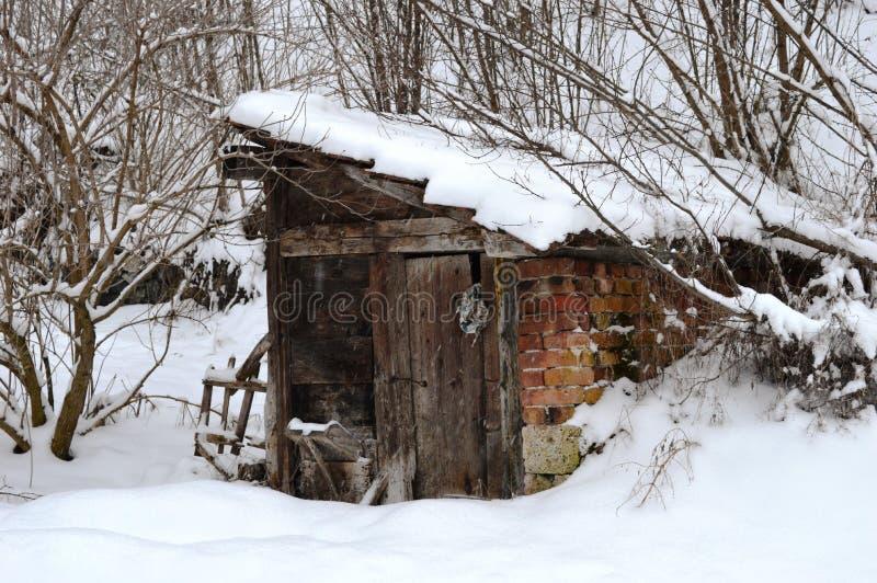 Une petite maison en bois dans la neige image libre de droits