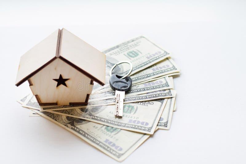 Une petite maison se trouve sur une fan de cent billets d'un dollar Les clés à la maison achetée Copie réduite de la maison photos stock