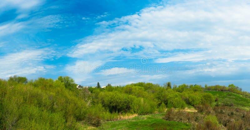 Une petite maison sur une colline sur un fond des arbres verts et un ciel bleu avec des nuages images libres de droits