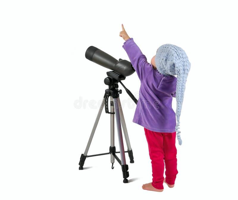 Une petite petite fille regardant par la portée et le pointin de tache photographie stock libre de droits