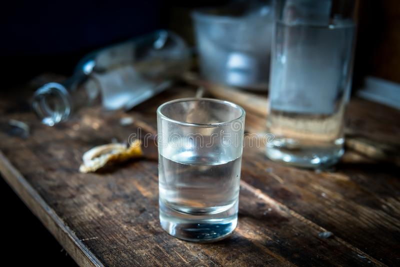 Une petite pile de fin de vodka sur la vieille table en bois sale photos libres de droits
