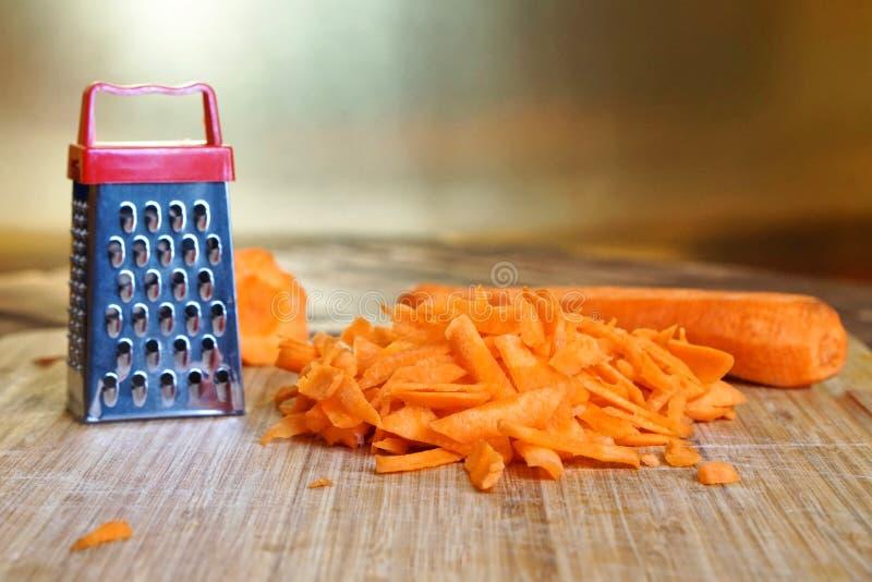 Une petite râpe et une grande carotte sont sur la planche à découper Mystère peu commun et illusion optique photos libres de droits