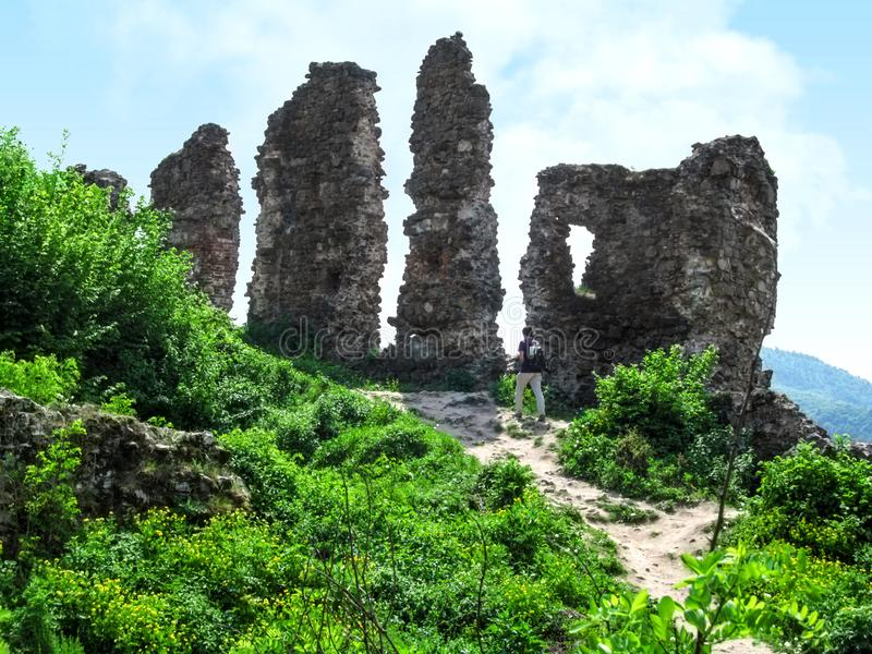 Une petite silhouette de l'homme près des hauts restes des murs d'un château médiéval détruit dans Khust, Ukraine photographie stock libre de droits