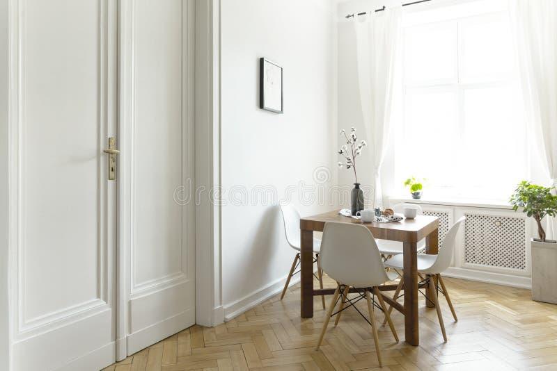 Une petite table de salle à manger en bois avec des chaises dans un intérieur ensoleillé de pièce avec les murs blancs, la porte  image stock