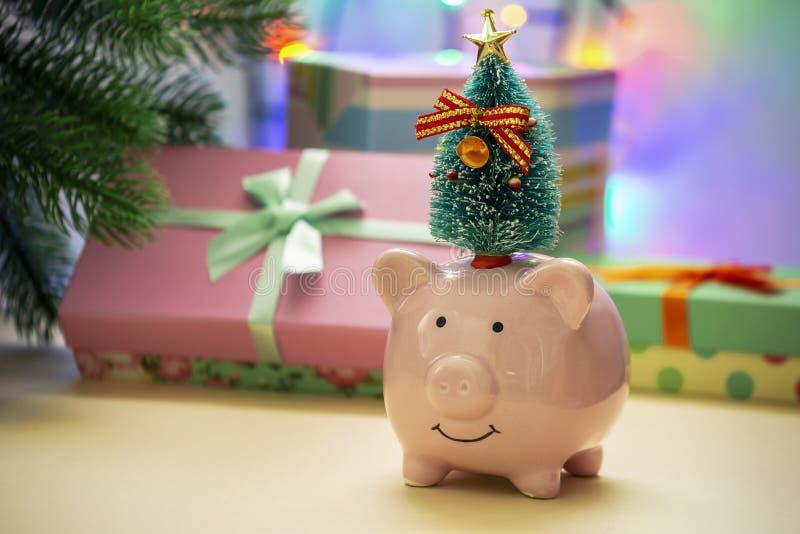 Une petite tirelire en céramique avec un arbre de Noël À l'arrière-plan dans une tache floue d'une guirlande et des cadeaux du `  photographie stock