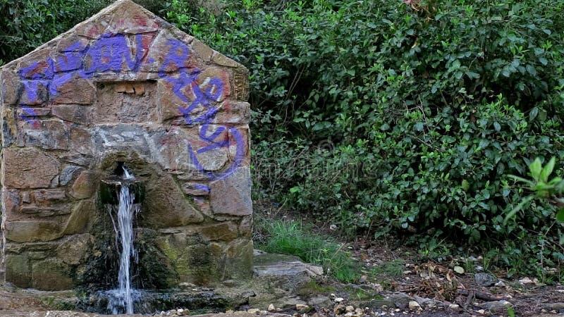Une petite vieille structure en pierre dont l'eau verse photo stock
