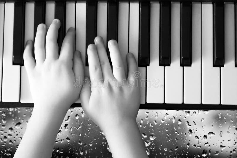 Une photo d'un adulte et d'une main du ` s d'enfant sur un clavier de piano, baisses sur un verre image libre de droits