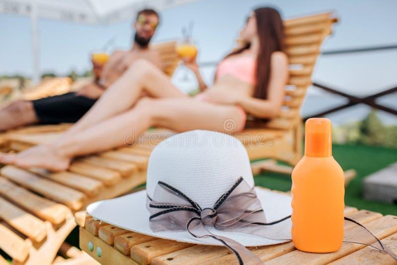 Une photo de bouteille orange et de chapeau se trouvant sur la petite table en bois Le couple se repose derrière lui Ils regarden photographie stock