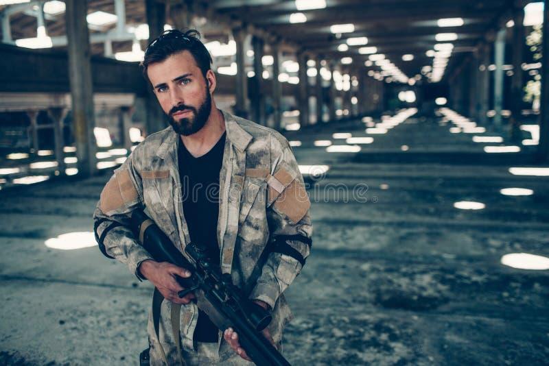 Une photo de l'homme sérieux et concentré regardant sur l'appareil-photo Il pose avec le fusil dans des mains photos libres de droits