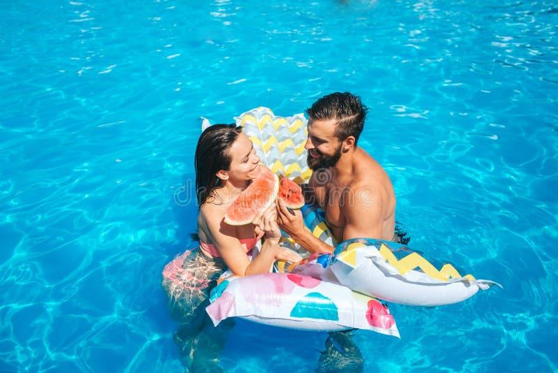 Une photo de la natation de couples dans la piscine et du penchement au matelas d'air Ils regardent l'un l'autre Également le cou photographie stock