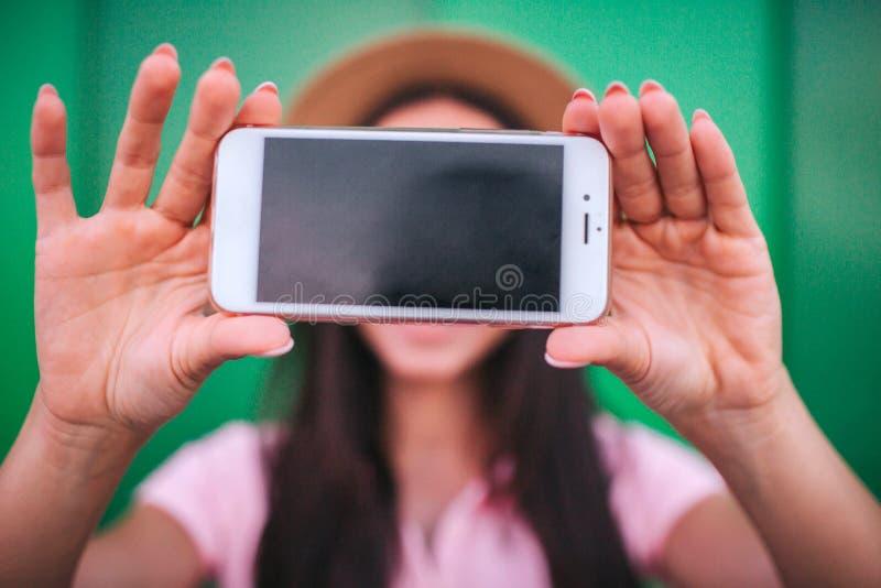 Une photo de téléphone que la fille tient dans des mains Il est blanc avec l'écran foncé sur le fond rayé et vert images libres de droits